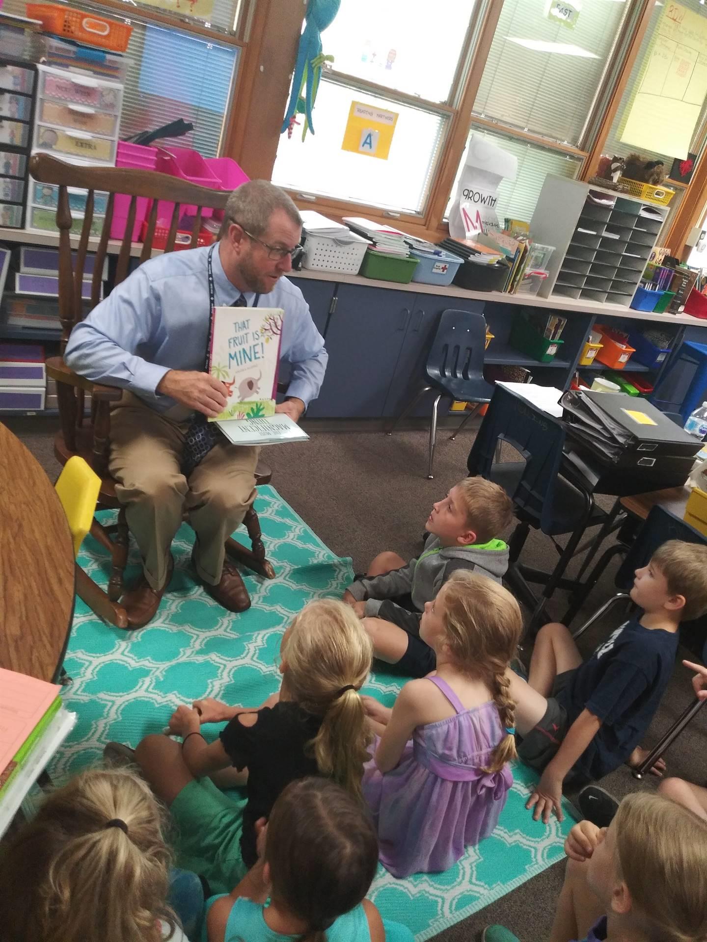 Superintendent Brown enjoying a book in Mrs. Mullins' classroom